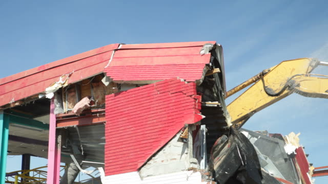 Excavator Demolishing a Building Roof and Wall