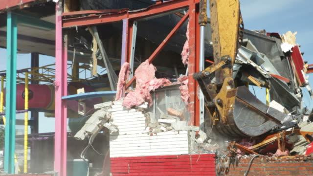 Excavator Demolishing a Building Wall