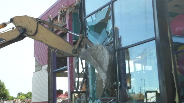 Excavator Demolishing Building Glass Wall