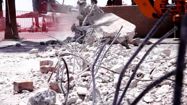 Excavator hydraulic jackhammer breaks concrete