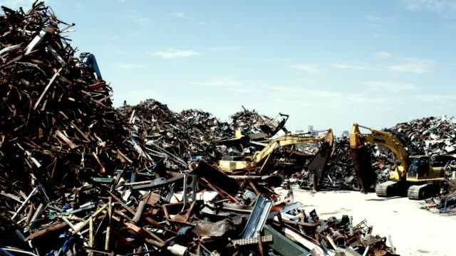 MS Excavator moving junk scrap metal to pile, Dallas, Texas, USA