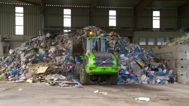 Excavator Moving Pile Of Paper Waste
