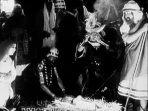 Excerpts from early silent film regarding the birth of Jesus / Shepherds men in robes and headdresses bowing kneeling to angels hovering overhead /...