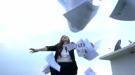 Excited businesswoman throwing papers in the air