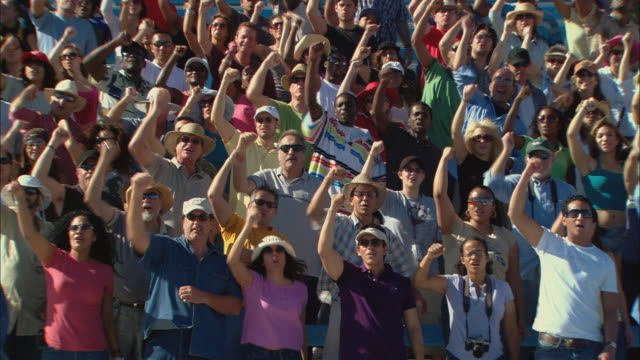 HA WS PAN Excited crowd clapping, cheering, and punching fists in air in bleachers / Homestead, FL, USA