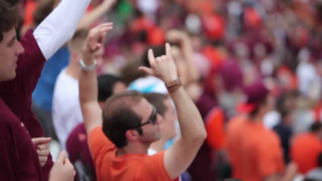 Excited fans jump up and down for home-team at college football game