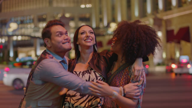 Excited friends on Vegas vacation jump up and down and share group hug.