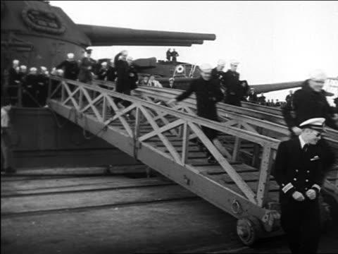 B/W 1945 excited sailors running down gangplank of military ship / WW II homecoming / documentary