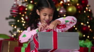 MS TU Excited Young Girl Opening Christmas Present / Richmond, Virginia, USA