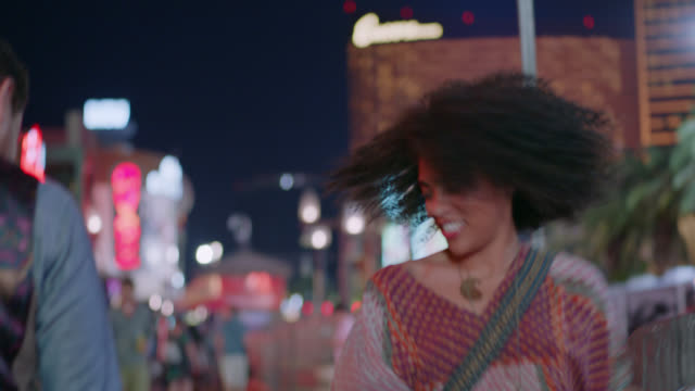 MS. Excited young woman spins around in circles on Las Vegas strip.