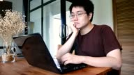exhausted man with eyeglasses working on laptop computer in living room - home office concept