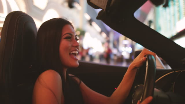 Exited female in convertible driving trough downtown Las Vegas