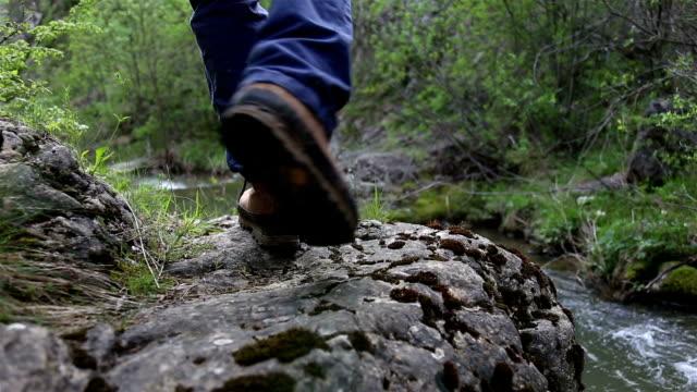 Explorer loopt op een rotsachtig pad door de rivier - achteraanzicht