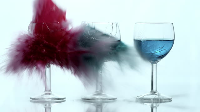 SLO MO explosion of wine glasses filled with colored liquid