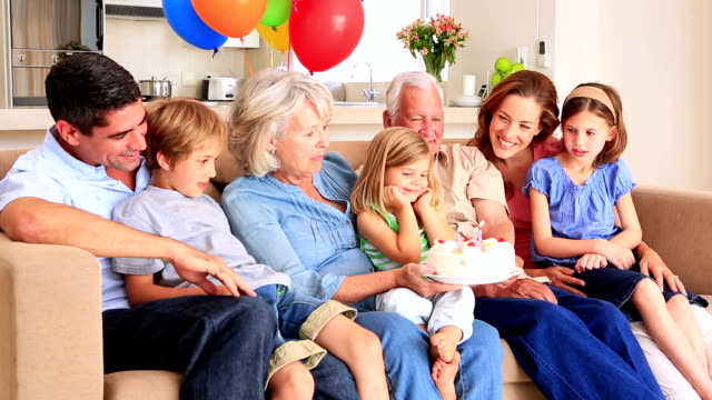 Extended family celebrating birthday together on couch