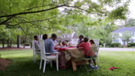 Extended family eating at picnic under tree