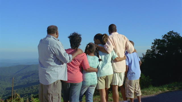 MS Extended family standing arm in arm and looking at landscape / Asheville, North Carolina, USA