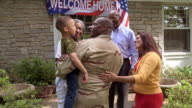 Extended family welcoming military man returning home