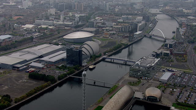 Exterior aerial shots along the River Clyde in Glasgow passing the Finnieston Street Bridge Glasgow Armadillo Clyde Auditorium the SEE Hydro and the...