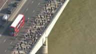 Exterior aerial shots large crowds of commuters walking over London Bridge on their way to work during London Underground strike morning rush hour on...