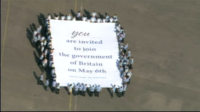 Exterior aerial shots of a Conservative party poster stunt featuring lots of people holding out a sheet featuring the words 'You are invited to join...