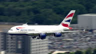 Exterior aerial shots of British Airways A380 plane landing at Heathrow Airport for the first time and taxiing along the runway after touching down...