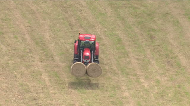 Exterior aerial shots of farming activity including dairy cattle in a field a tractor moving hay bales and various farm buildings and fields on 21...
