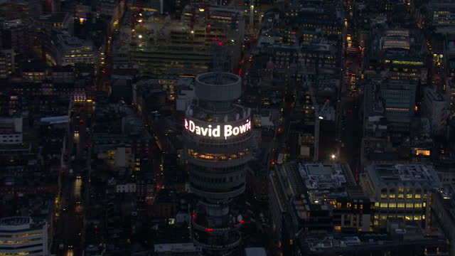 Exterior aerial shots of the BT Tower in London at dusk displaying a digital message 'Rest in Peace David Bowie' on January 11 2016 in London England