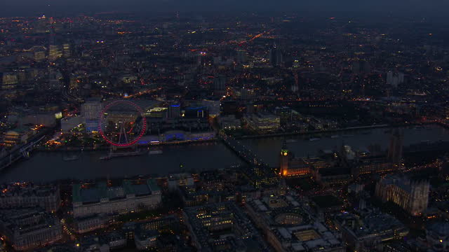 Exterior aerial shots over London at nightfall including the London Eye and Houses of Parliament on January 11 2016 in London England