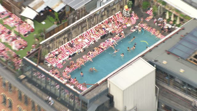 Exterior aerial shots people sunbathing and swimming in rooftop swimming pool at the Shoreditch House members club on July 01 2015 in London England