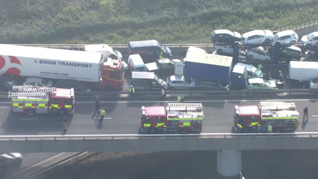 exterior aerials traffic jam leading onto Sheppey Crossing Bridge and fire engines on bridge next to pile up involving dozens of cars and lorries inc...