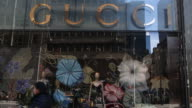 Exterior and signage shots of a Gucci store location in New York NY Shoppers and commuters wearing warm winter clothing walk past the entrance to a...