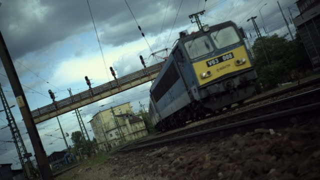 Exterior day, tilted shot of a train passing the camera on its right side