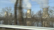 Exterior driving shot past ressidential houses and cooling towers reactor housings and pylons of Three Mile Island nuclear power station on March 01...