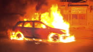 Exterior driving shots past several burning cars during a period of civil unrest in Baltimore on April 28 2015 in Baltimore Maryland