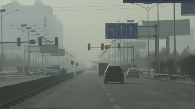 Exterior driving shots thorugh Beijing traffic on a smoggy day including shots of smoky exhaust pipes on December 01 2015 in Baoding China