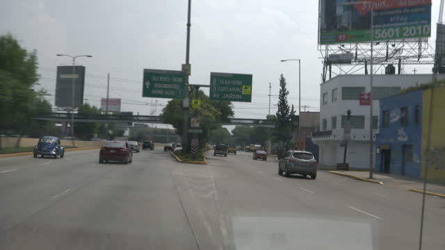 Exterior driving shots through Mexico City passing various businesses and graffiti covered signs on July 09 2015 in Mexico City Mexico