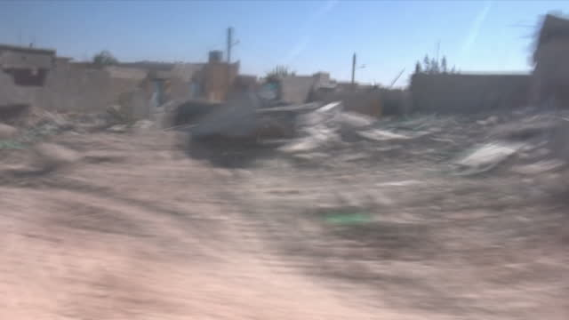Exterior driving shots through the rubble and ruined buildings of a liberated Raqqa on 17 October 2017