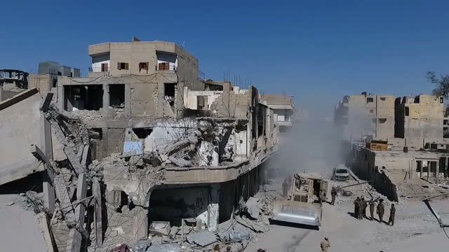 Exterior drone aerials of a devastated Raqqa as a bulldozer clears a path through a rubble strewn road YPG flags flying and damaged buildings on 19...