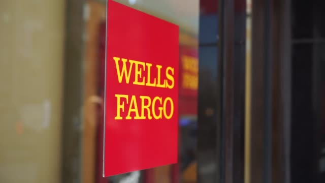 Exterior footage of a Wells Fargo in New York NY on April 13 2016 Shots wide shot from across the street of Wells Fargo as people walk and drive by...
