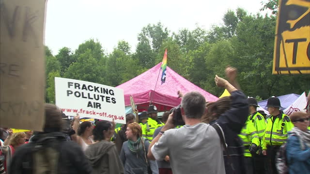 exterior general views protesters linking arms and holding signs trying to block lorries entering fracking drilling site with police officers moving...
