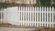 Exterior handheld POV of white picket fence in an older residential neighborhood.
