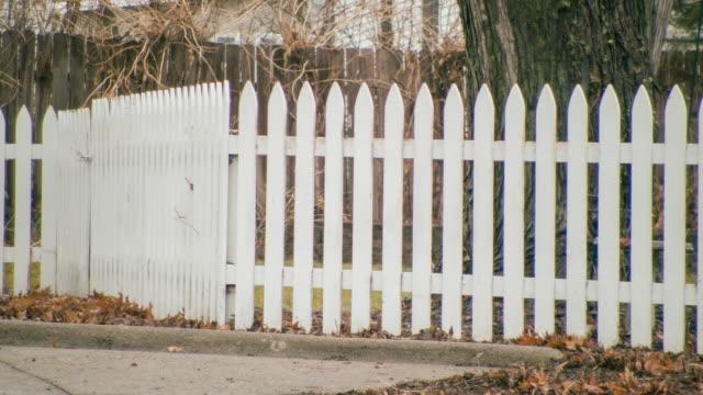 Exterior handheld POV of white picket fence in an older residential neighborhood.