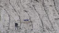 Exterior high shot group of people building snowman on snowy hillside man slips falls BelfasHeavy Snowfall Causes Travel Chaos Across UK on January...