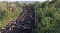 Exterior high shot migrants refugees crowd of asylum seekers walking along train tracks towards border with Austria on September 04 2015 in Bicske...