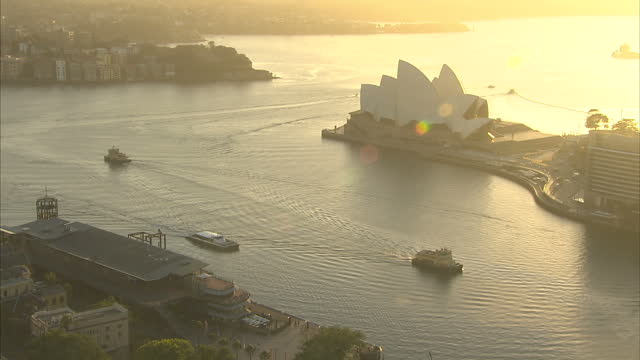Exterior high shot of boats in Sydney harbour near the Sydney Opera House lit by a golden early morning light>> on April 19 2014 in Sydney Australia