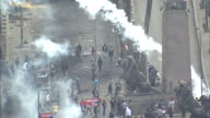 Exterior high shots large crowds of protesters surrounded by tear gas confronting a line of police with some throwing back tear gas canisters...