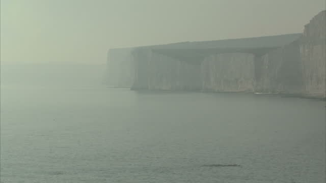 Exterior high shots over a beach at Beachy Head as people walk and paddle in the sea as a haze from a possible chemical leak hangs in the air on 28...
