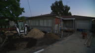 exterior house front yard renovation site at start of day dull light idle bobcat trenches piles of sand and dirt upturned wheelbarrow standing on end...