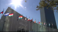 Exterior locked off shot UN building with the nations flags fluttering in the breeze United Nations Building Locked Off Exterior on September 25 2012...